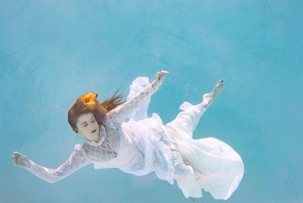 woman wearing white dress swimming