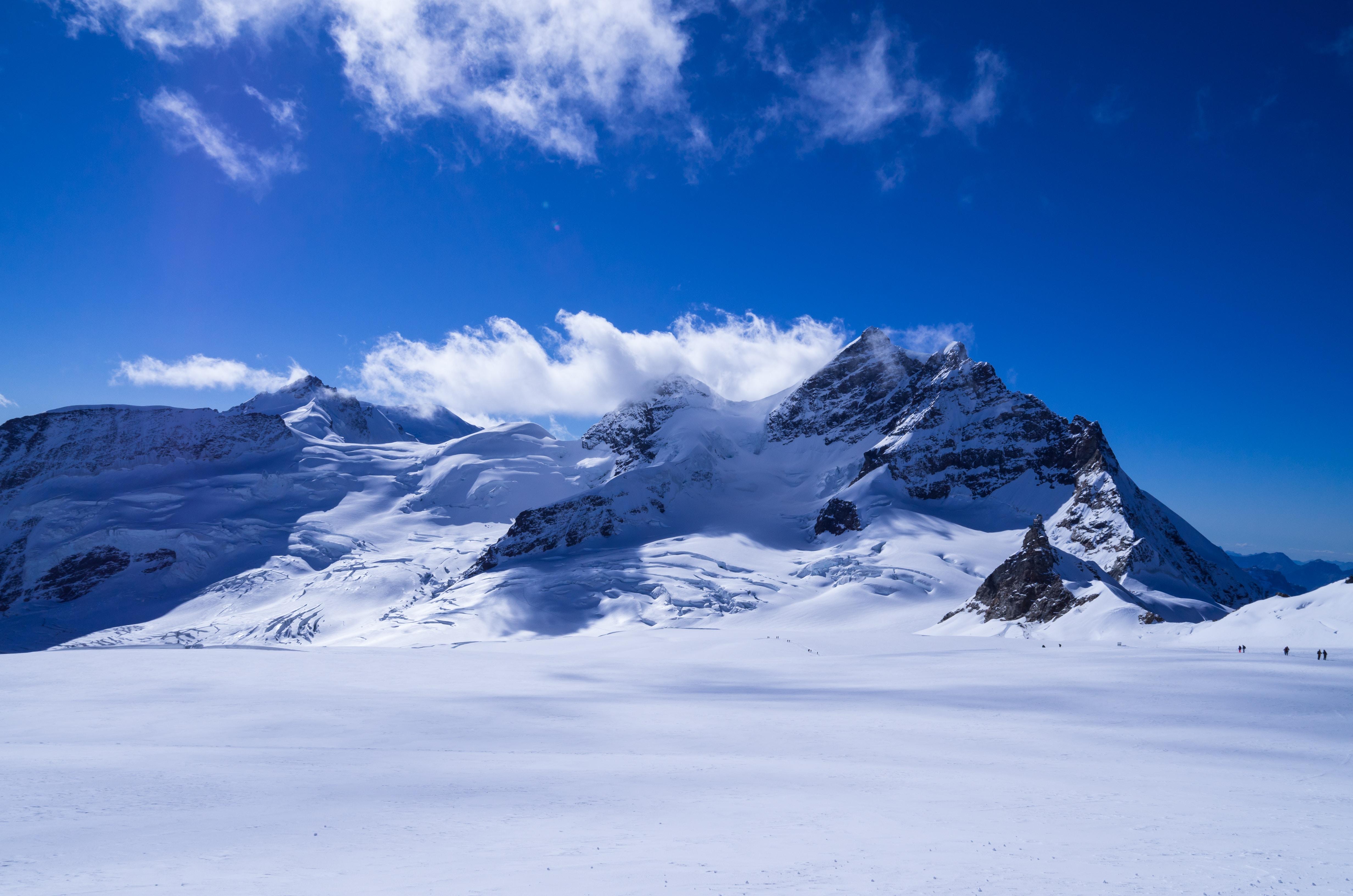 snow-covered mountain under calm blue sky