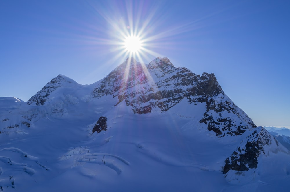 snow-covered mountain under clear blue sky