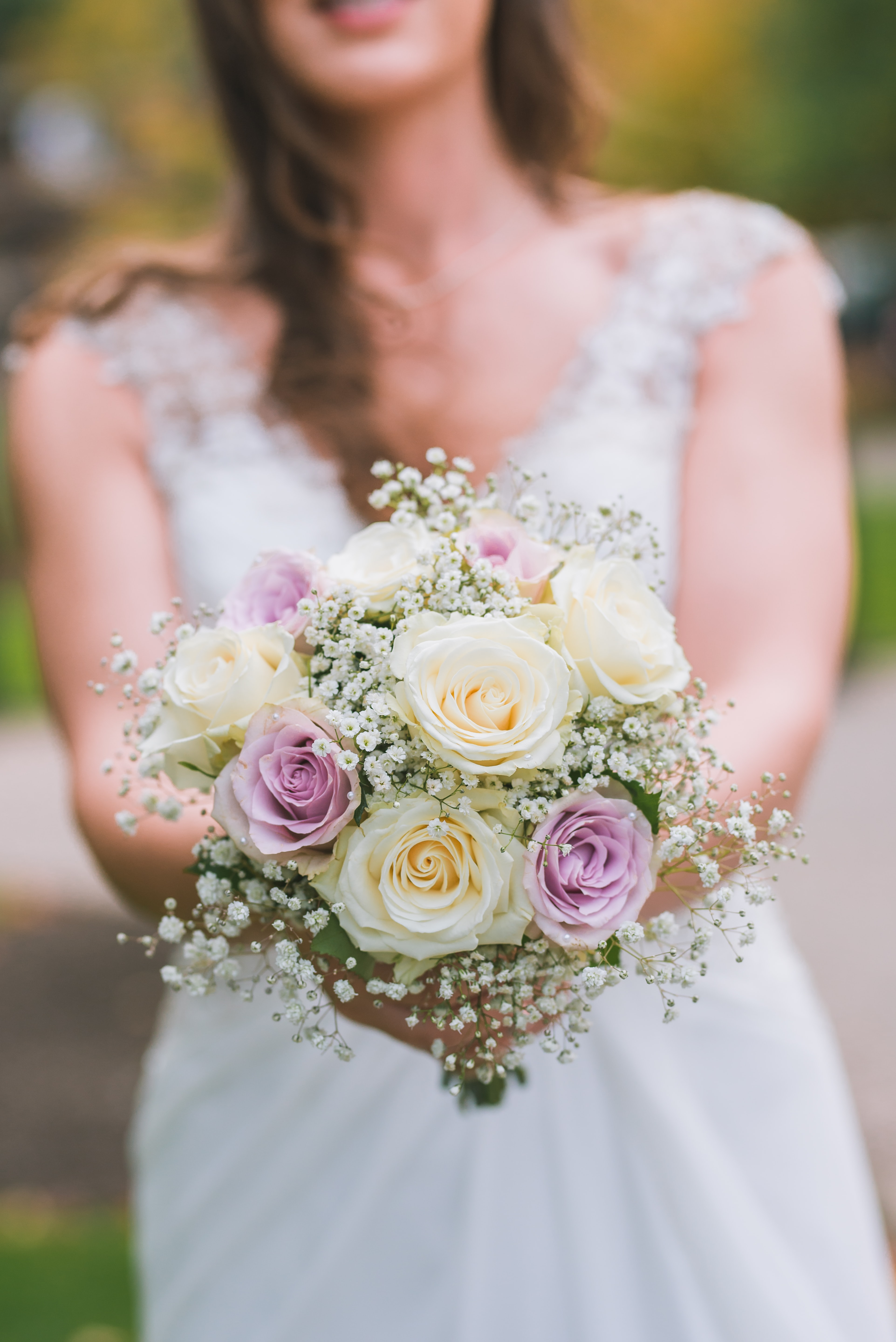 woman holding white and purple bouquet selective focus photography