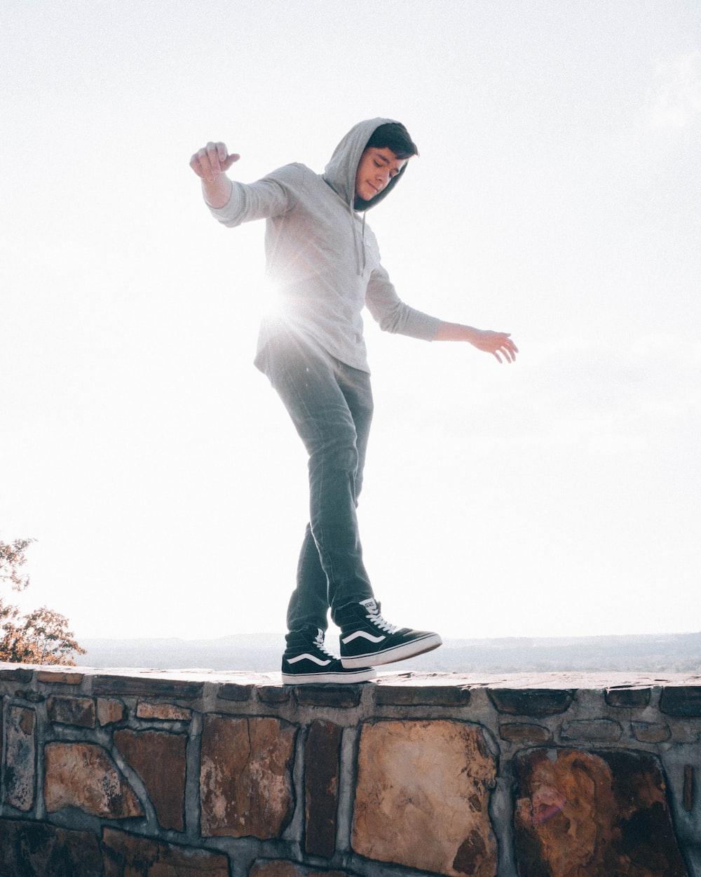 man wearing pullover walking on concrete wall