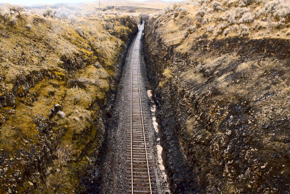 railway between brown rocky hills