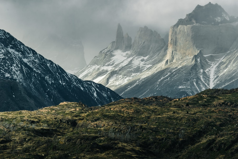 green hills near gray mountains