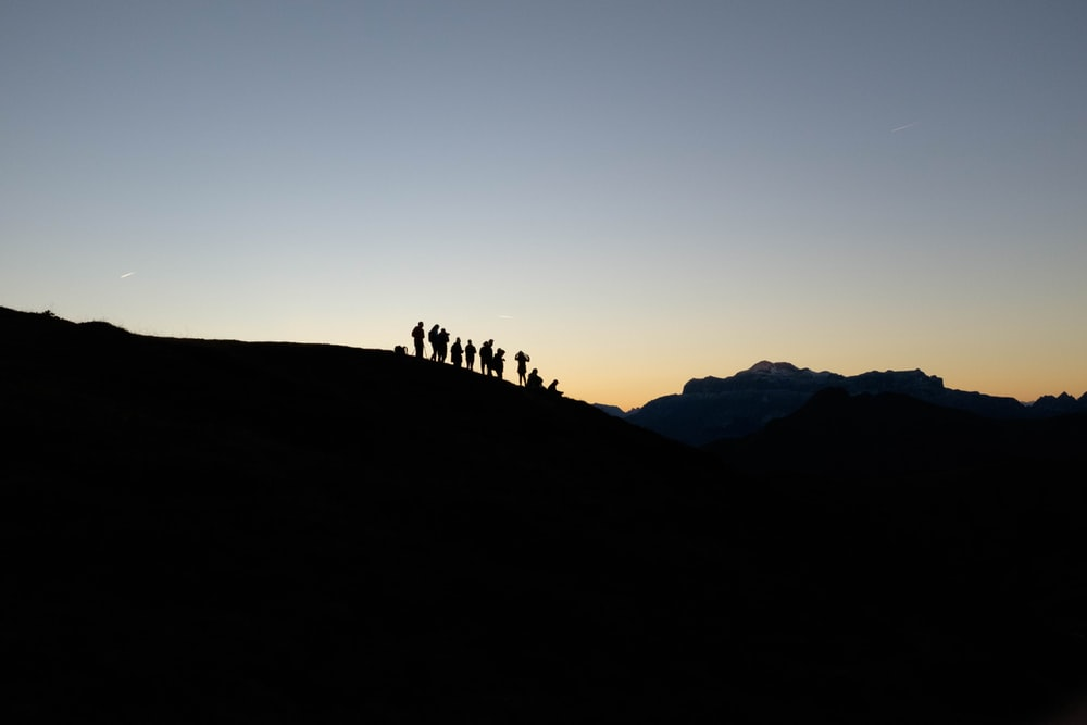 silhouette of people standing on mountain edge