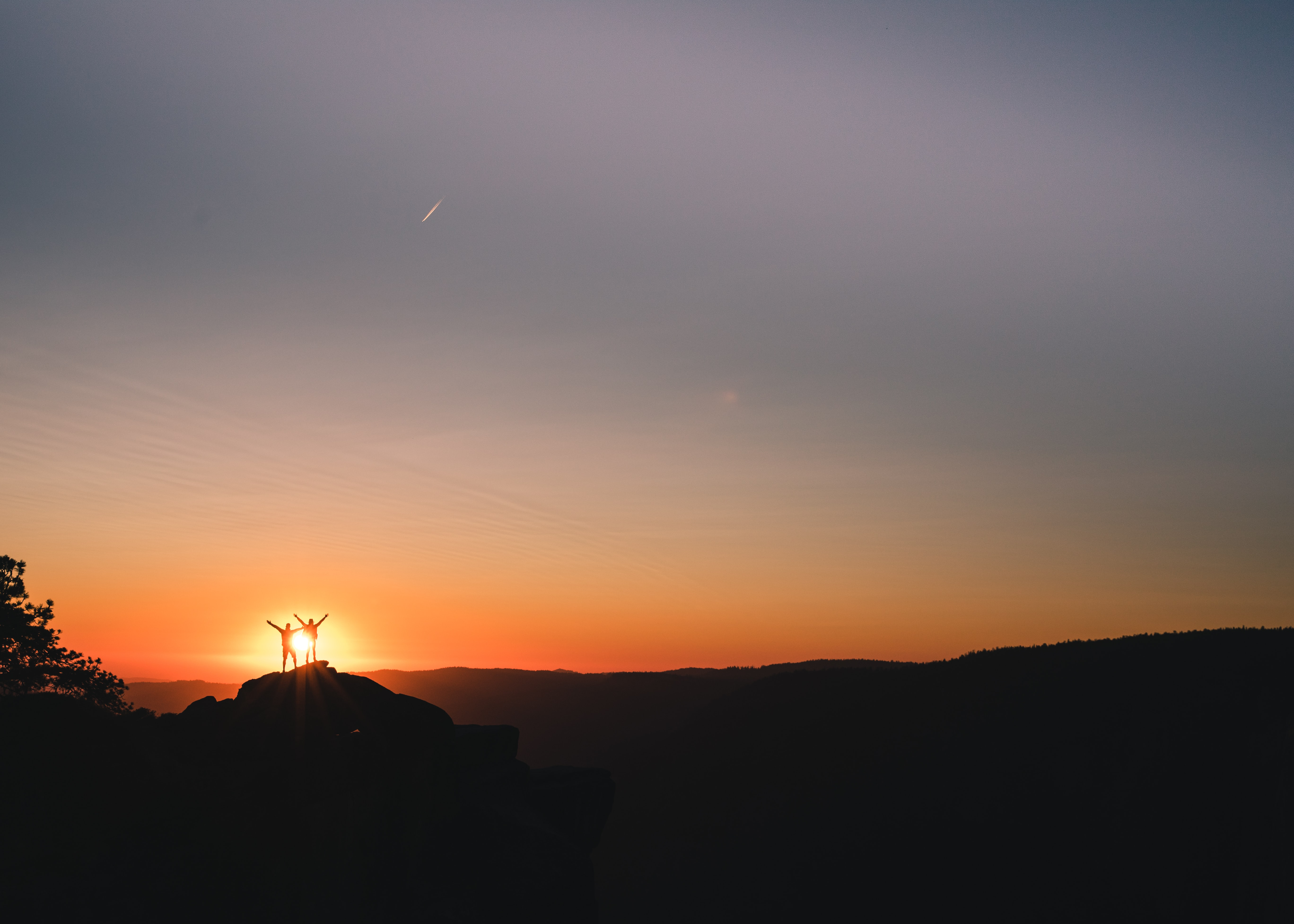 silhouette of couple on cliff during golden hour