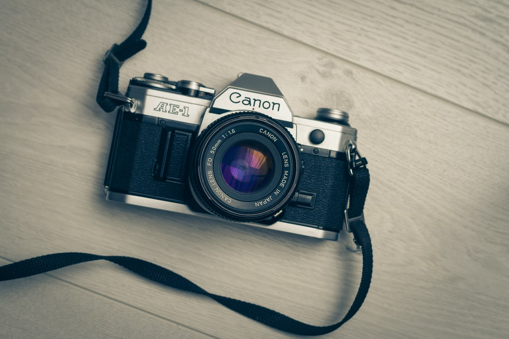 gray and black Canon AE-1 camera on wooden surface