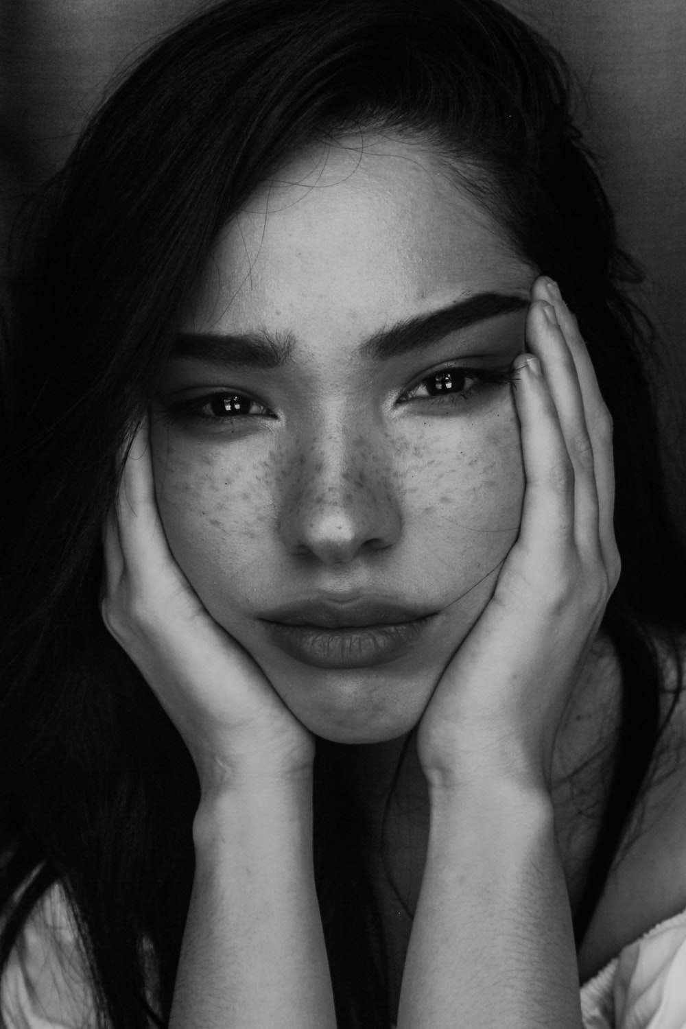 grayscale photography of woman with two hands on her face