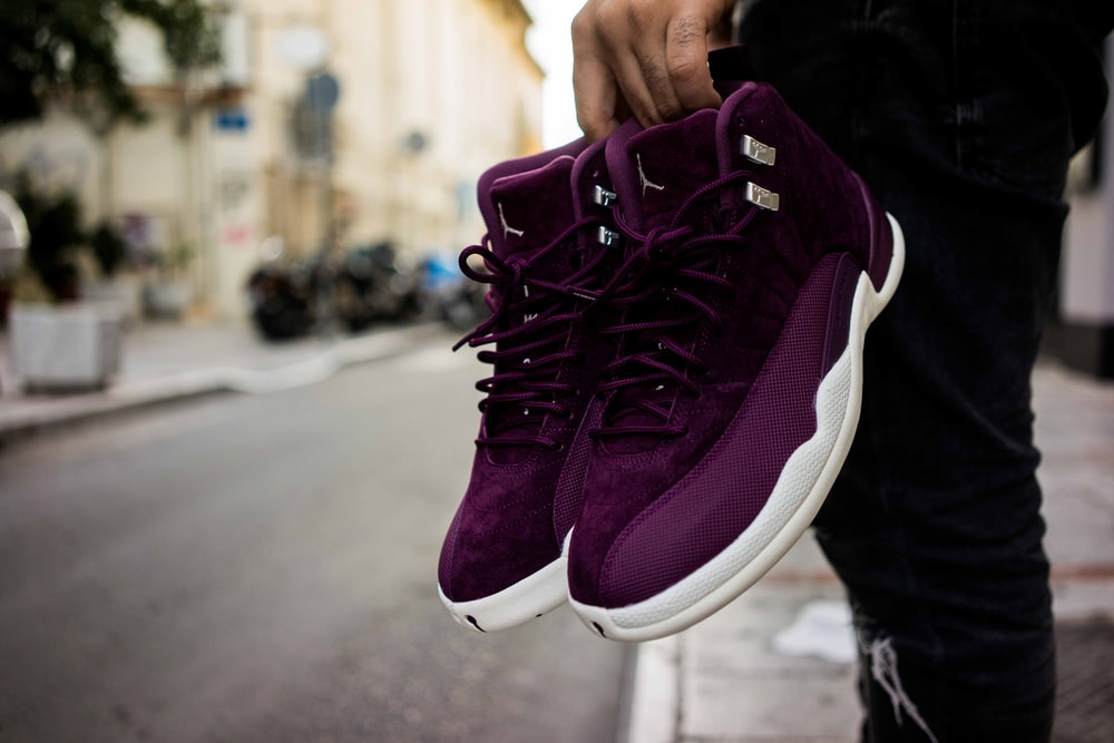 person holding Bordeaux Air Jordan 12's