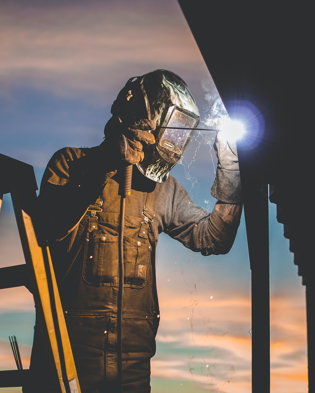 man on ladder welding post