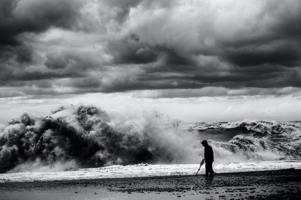 grayscale photo of man walking on seashore