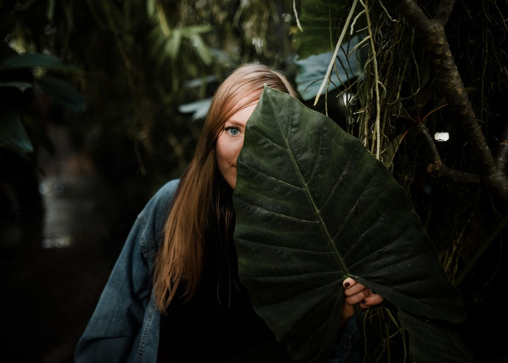 woman standing while covering her face with taro leaf
