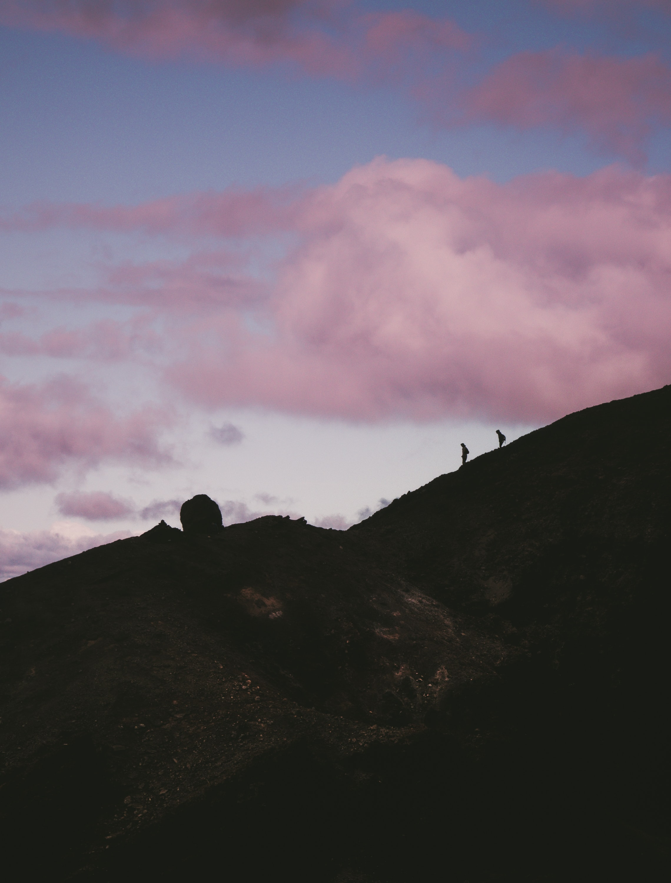 two silhouette of person walking down the hill
