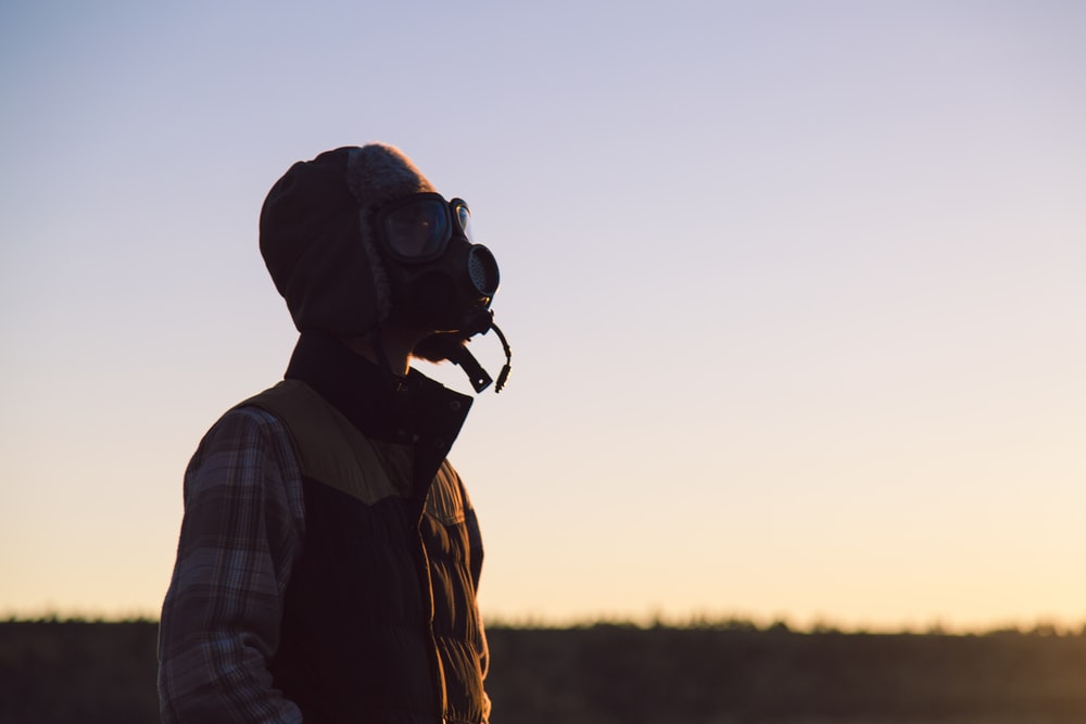 man standing on open field wearing respirator