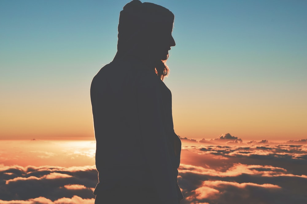 silhouette of person wearing hoodie on clouds