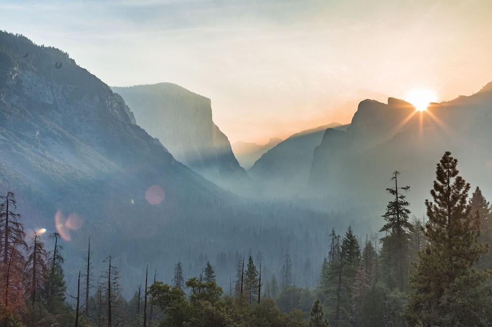 landscape photography of sun peeping on mountain range