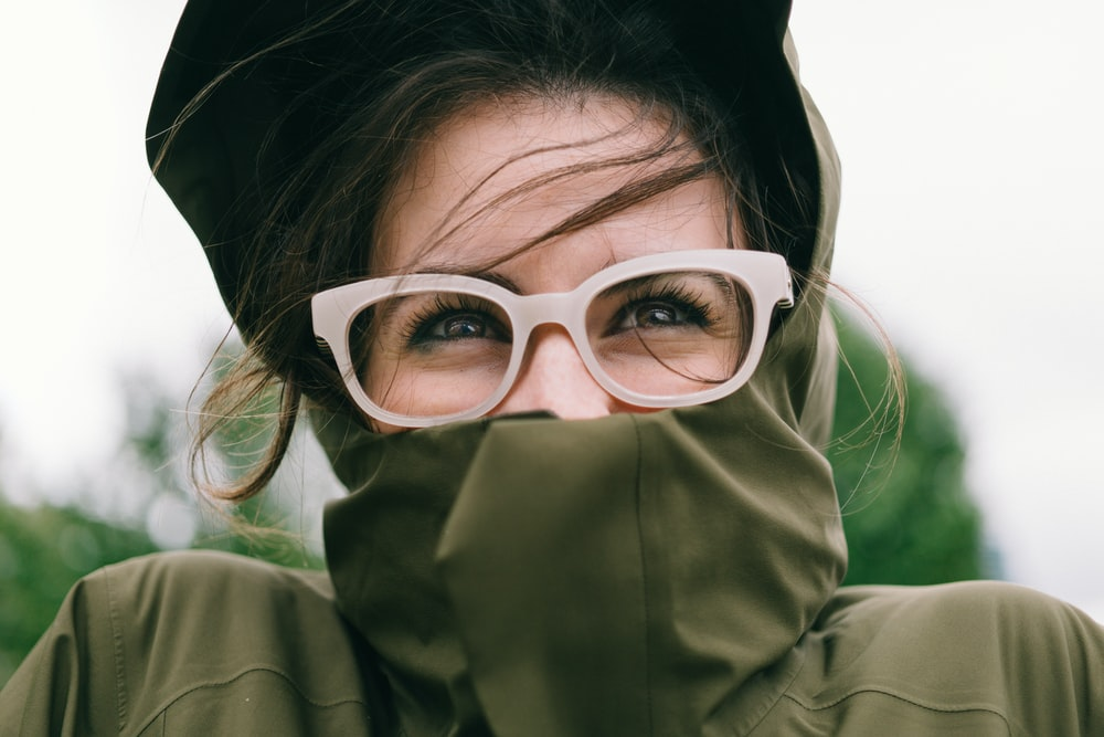 woman covering mouth with green turtleneck top