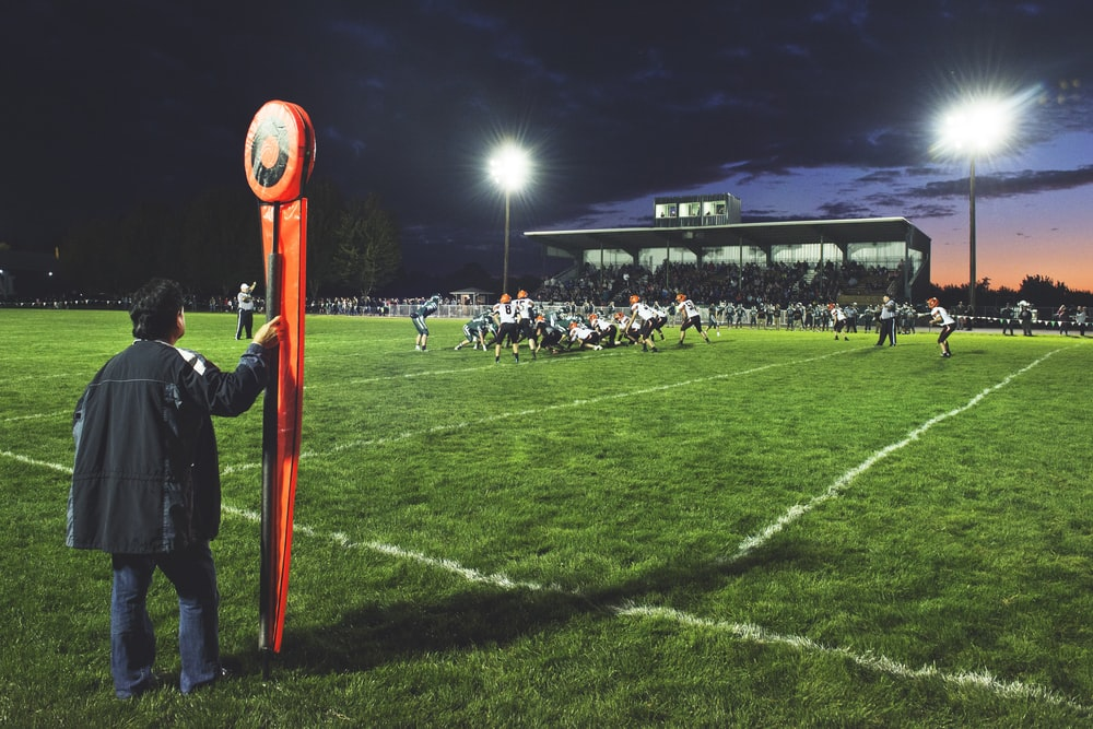 man holding football field post on side of field