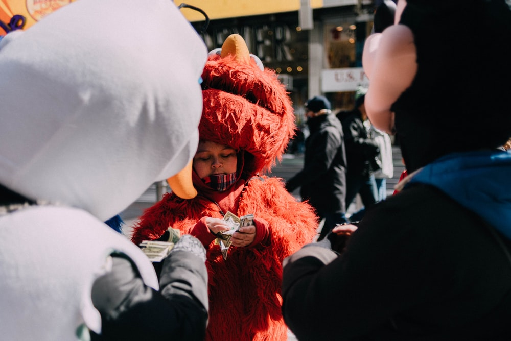person counting money in Elmo costume