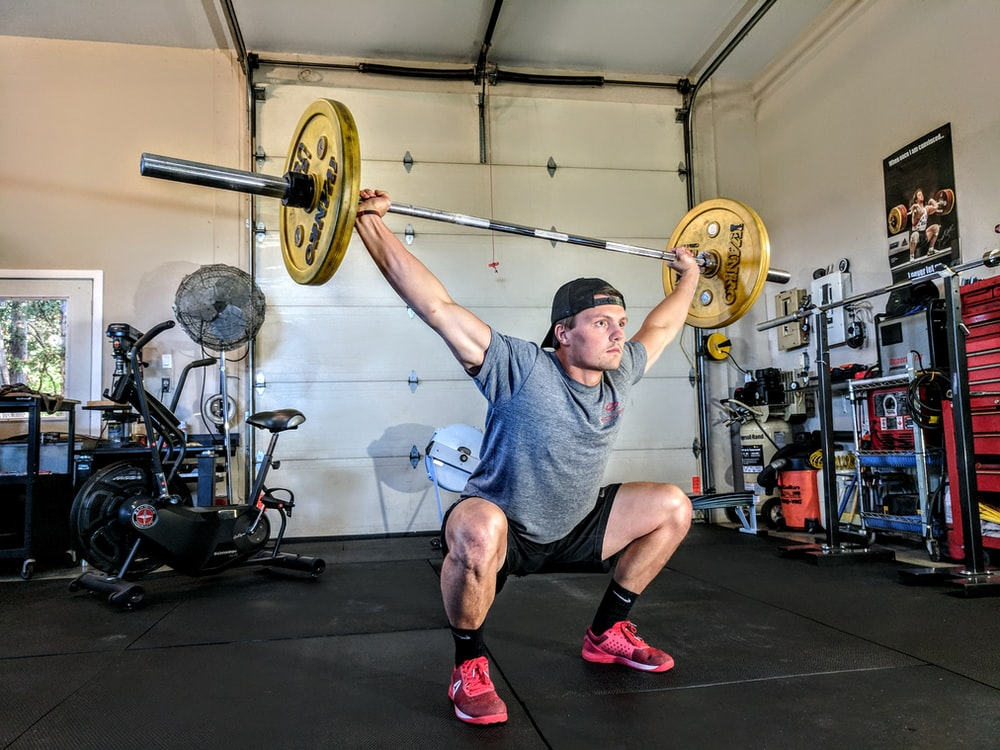 man lifting yellow barbell
