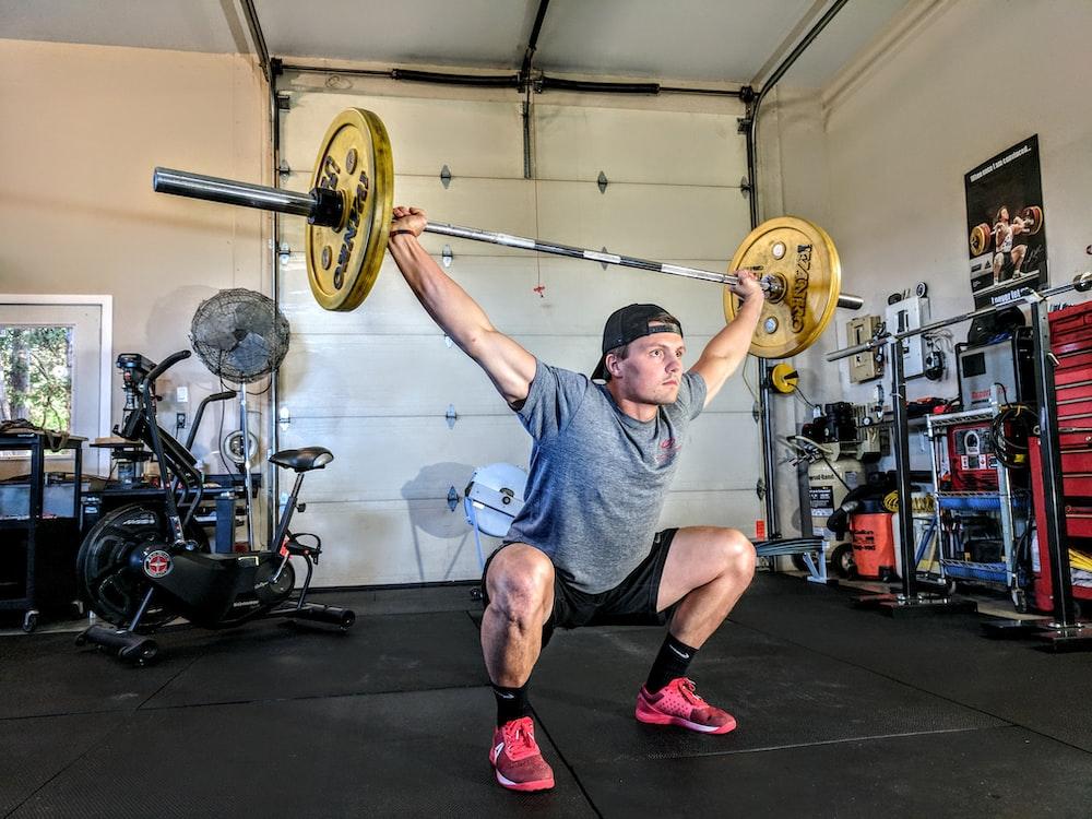 man lifting yellow barbell