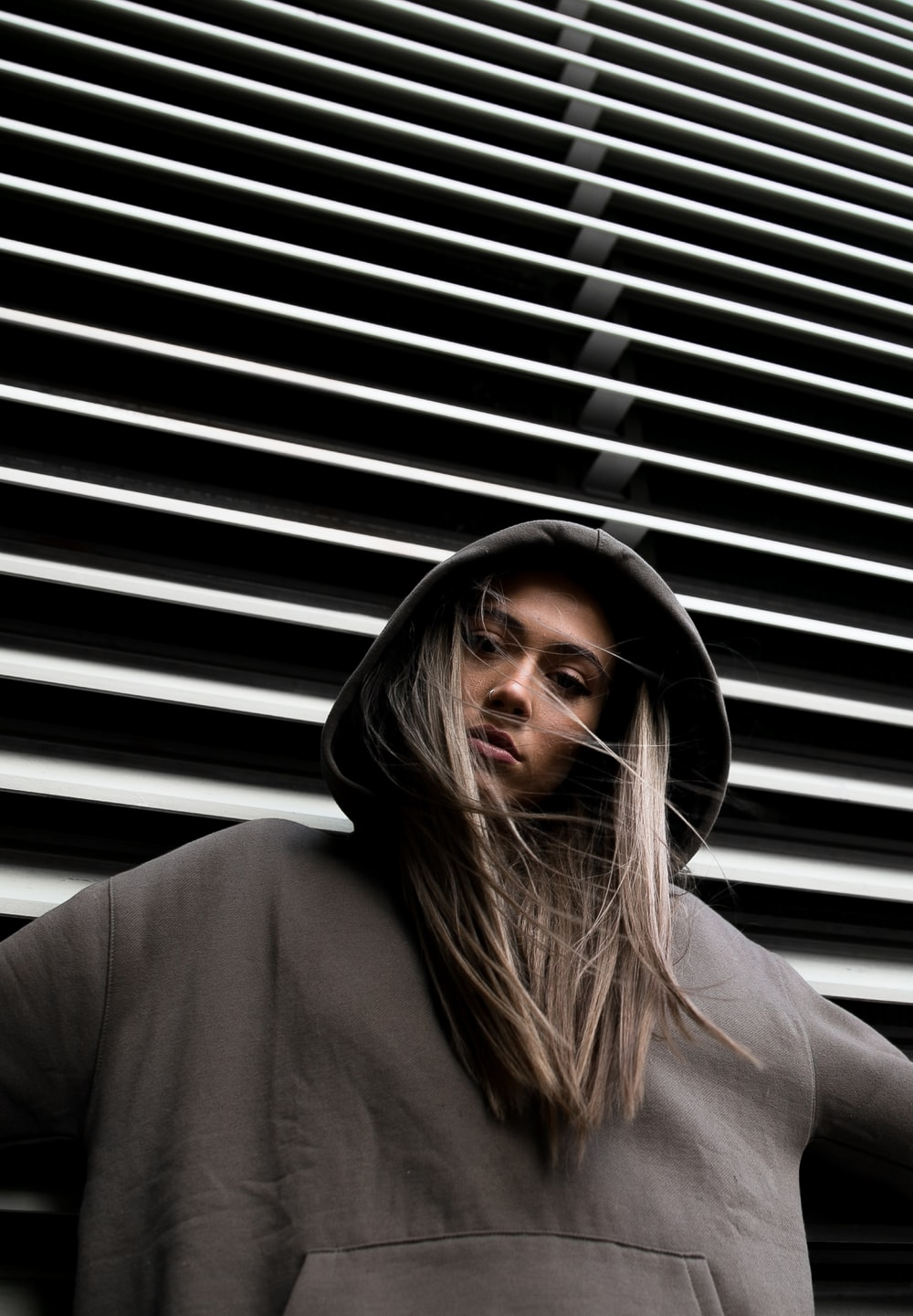 woman in hoodie standing in front of white wall