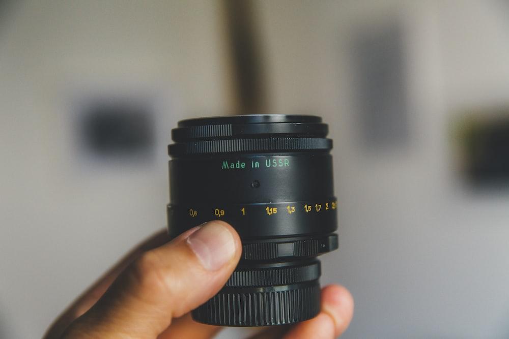 person holding black telephoto lens