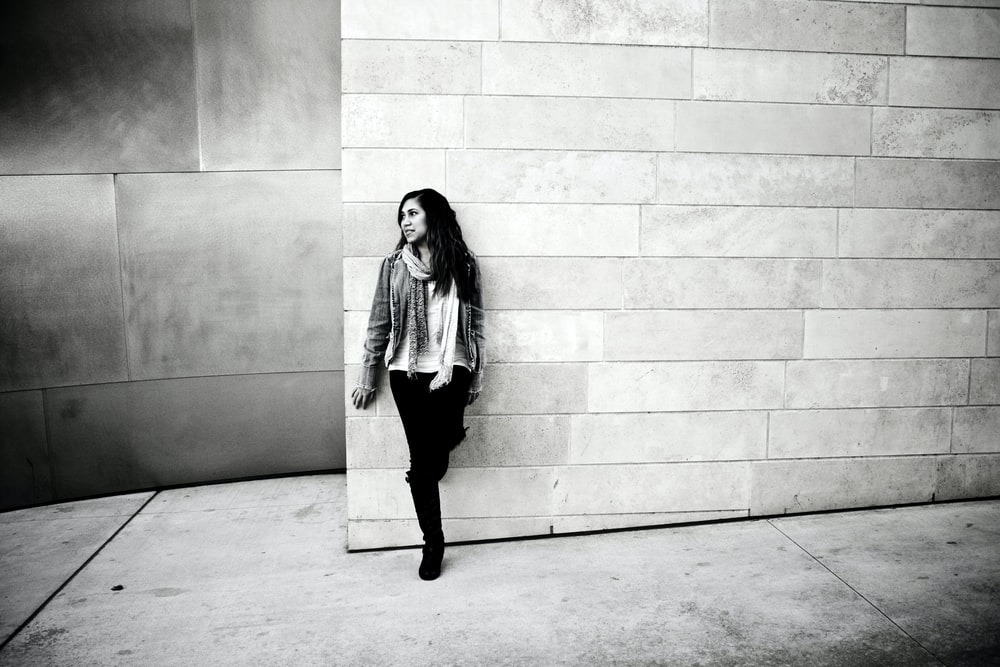 grayscale photography of woman leaning on wall