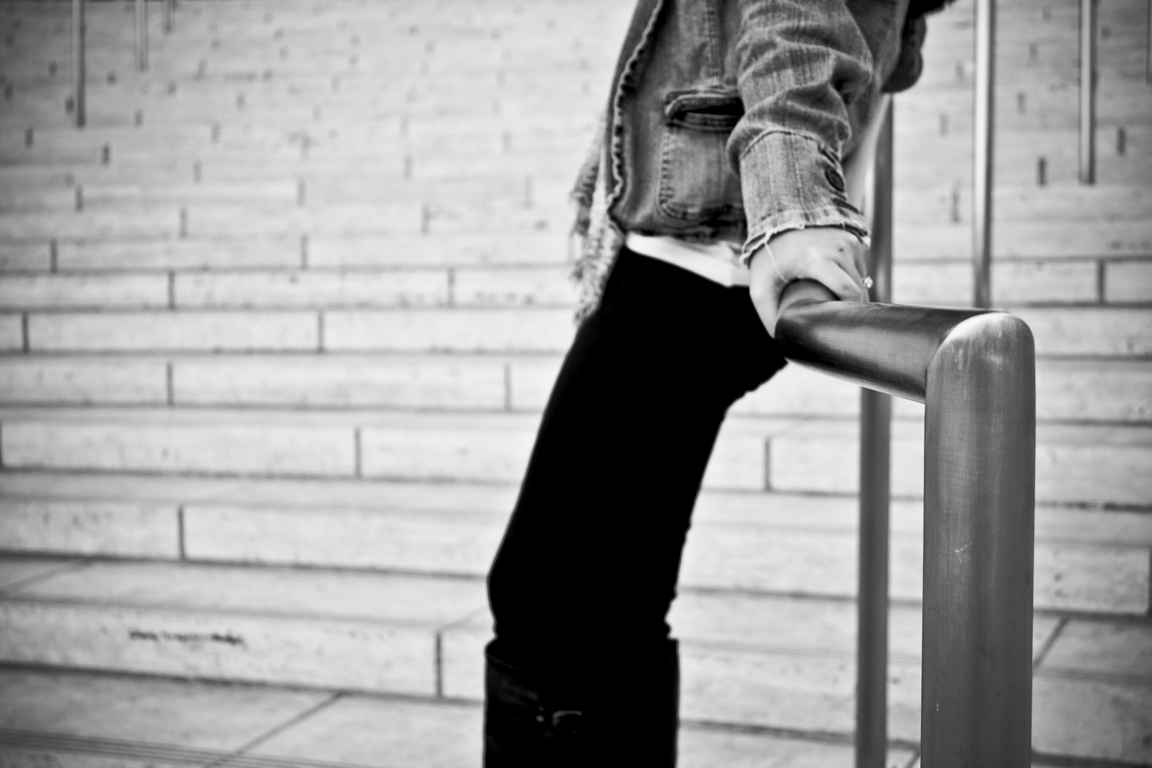 grayscale photography of person holding handrail