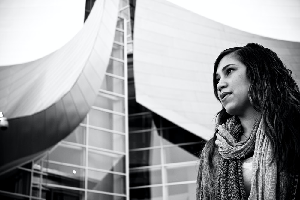 grayscale photo of woman beside building