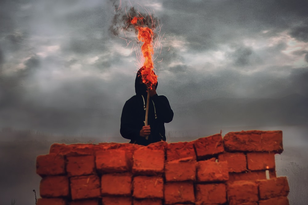 man holding torch light standing on red concrete rooftop