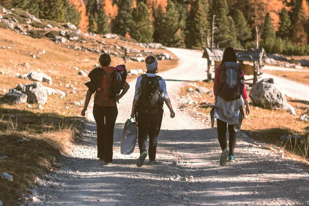 three person walking on mountain