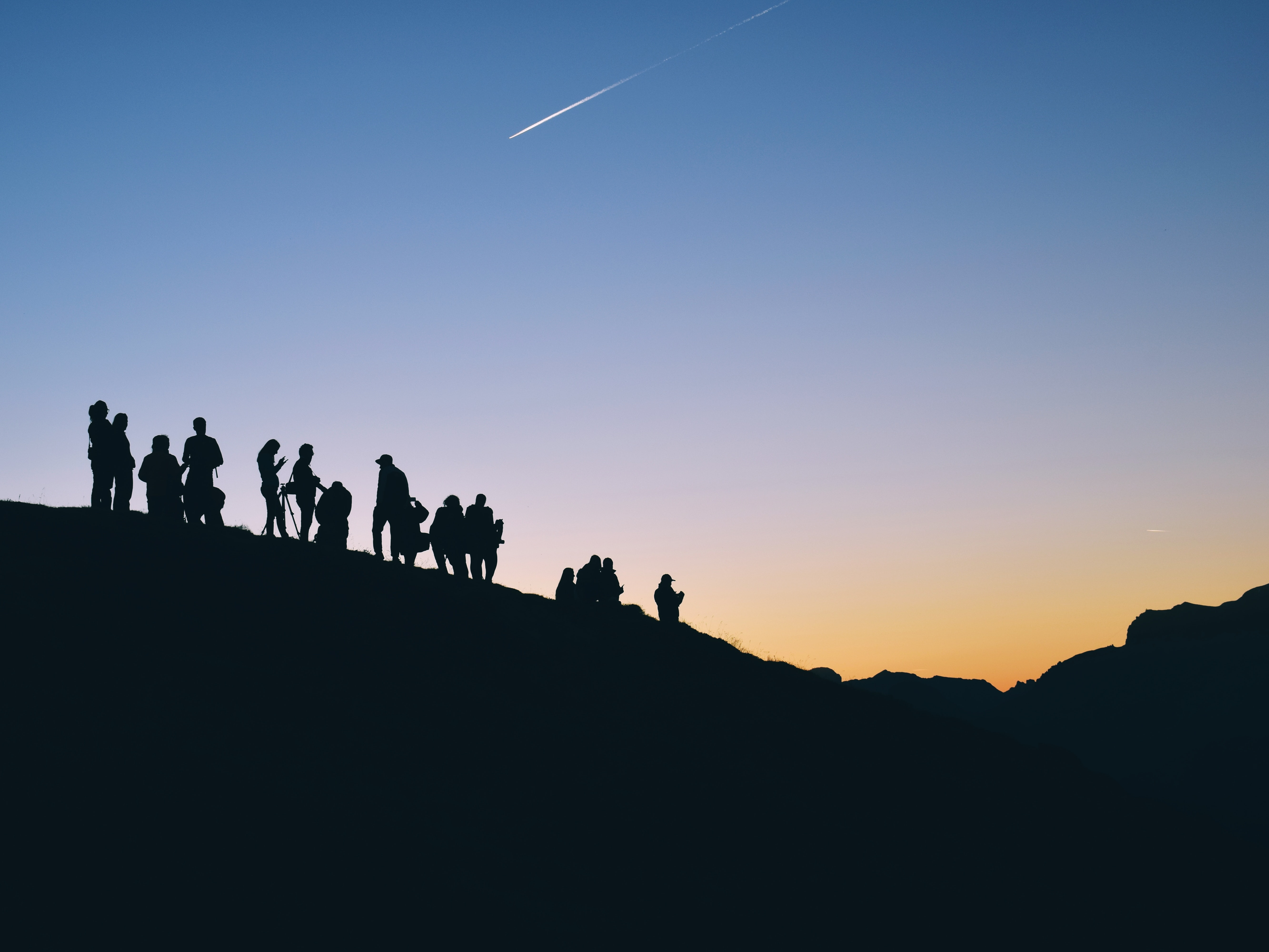 silhouette of people on mountain under falling satr
