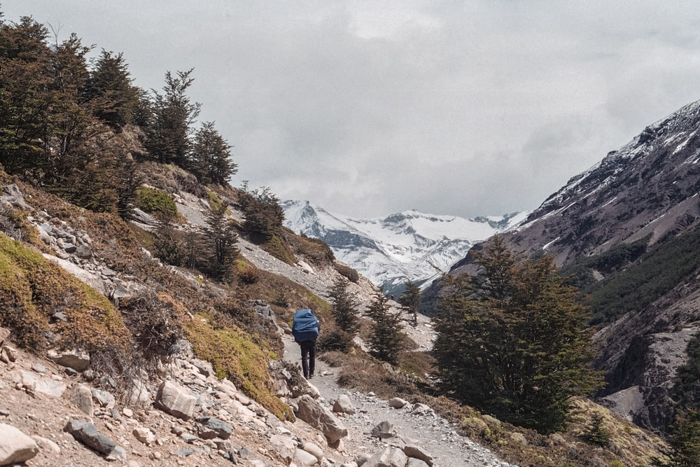 man walking on cliff under nimbus clouds