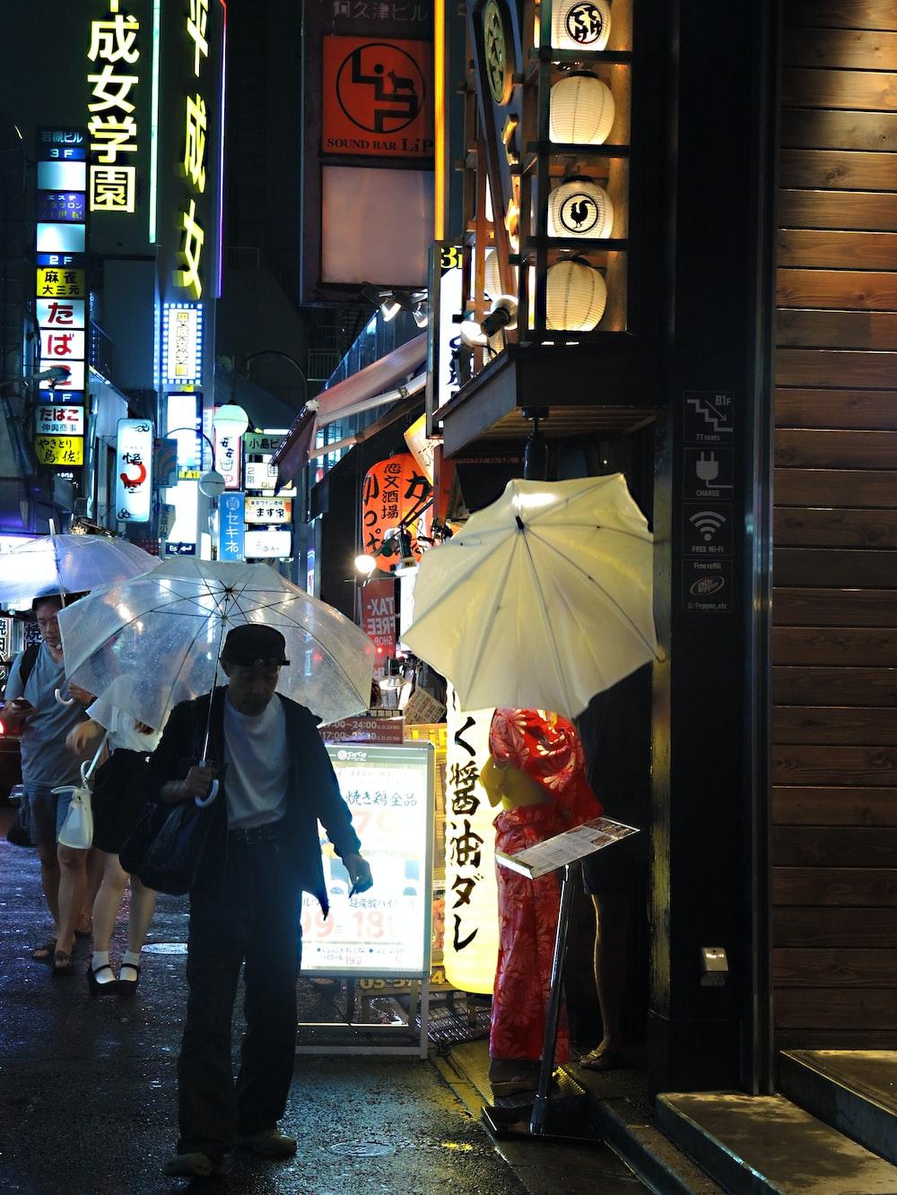 man in black jacket holding umbrella walking on street during nighttime