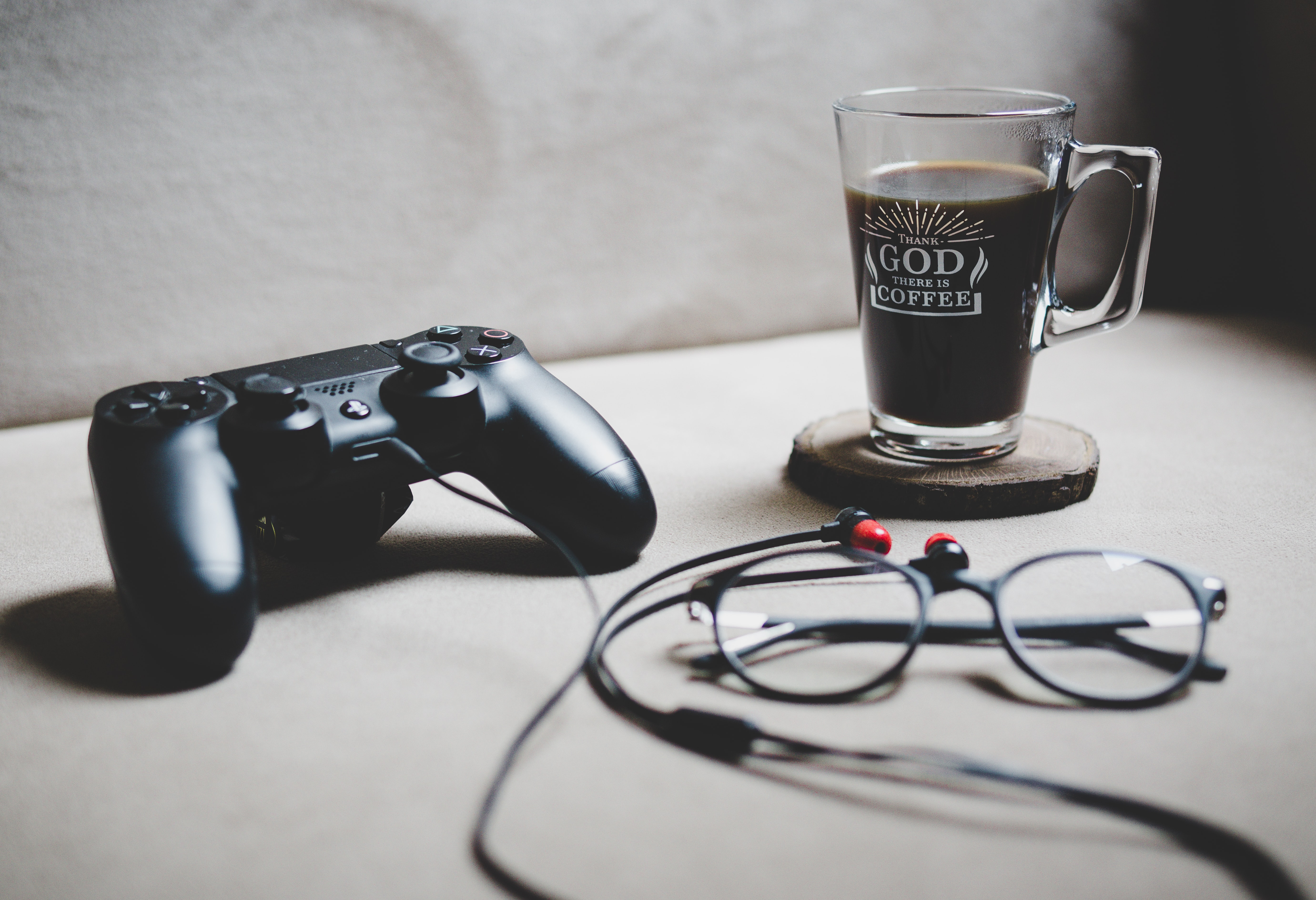 black Sony Dualshock 4 beside clear glass mug filled with coffee