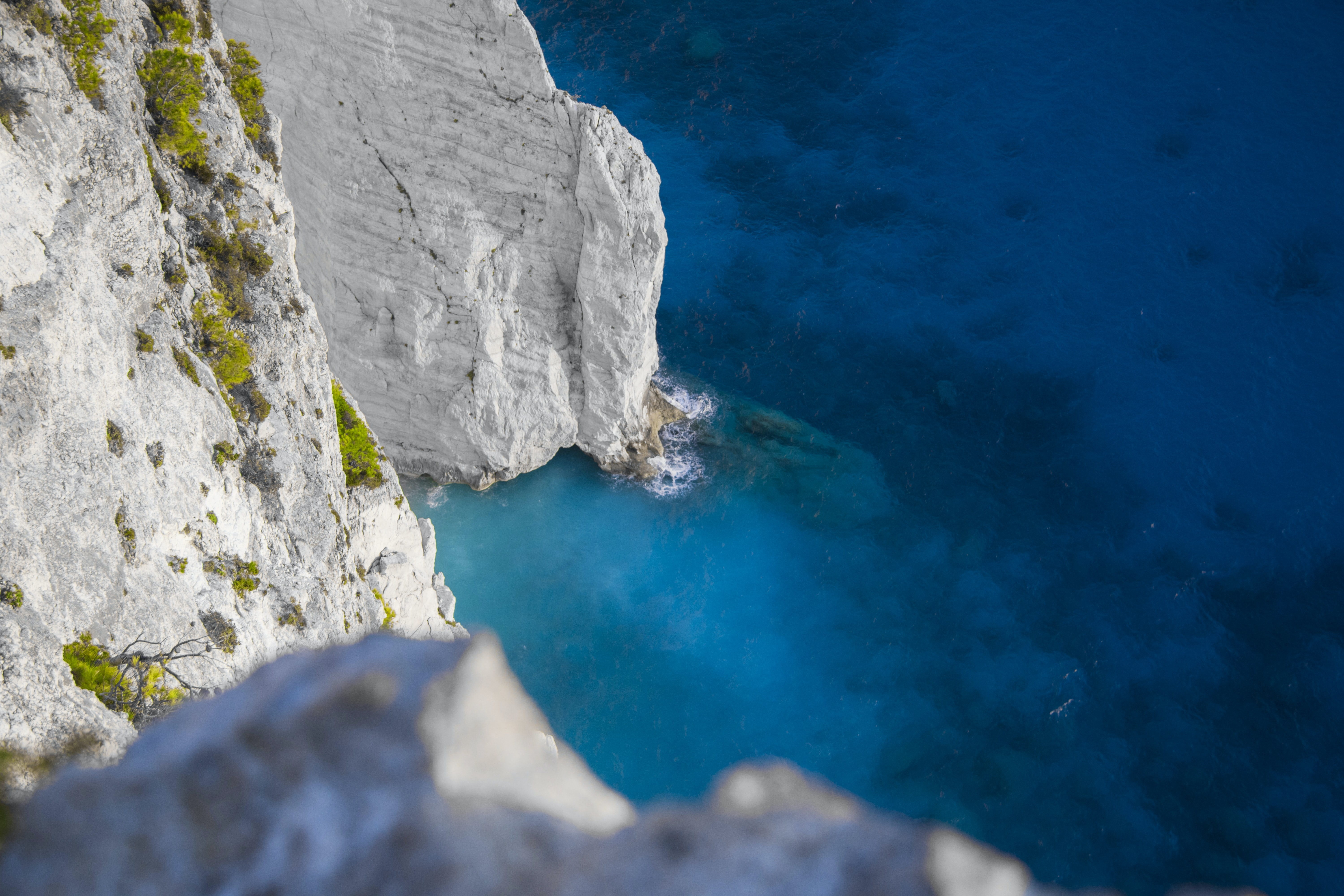 white and green cliff beside ocean