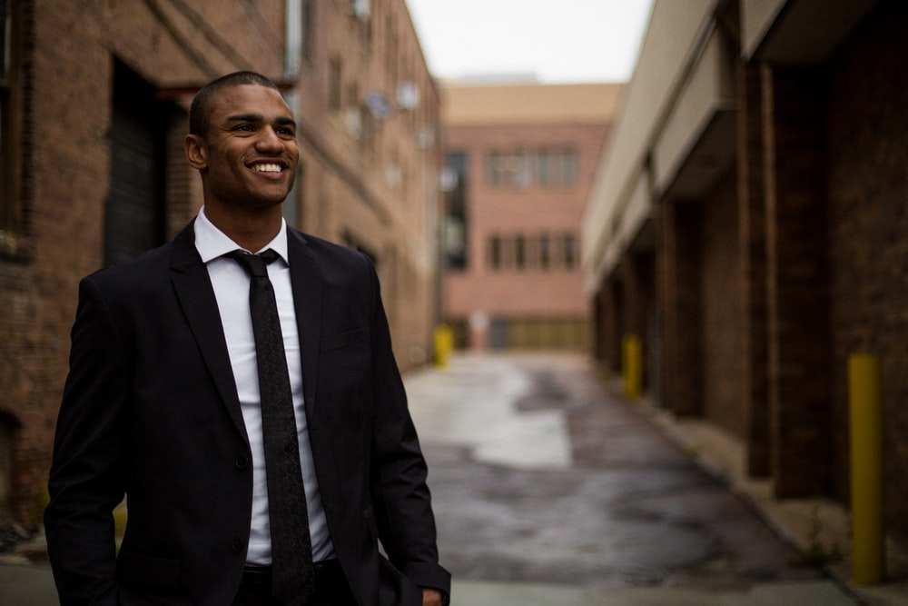 smiling man standing between brown concrete buildings at daytime