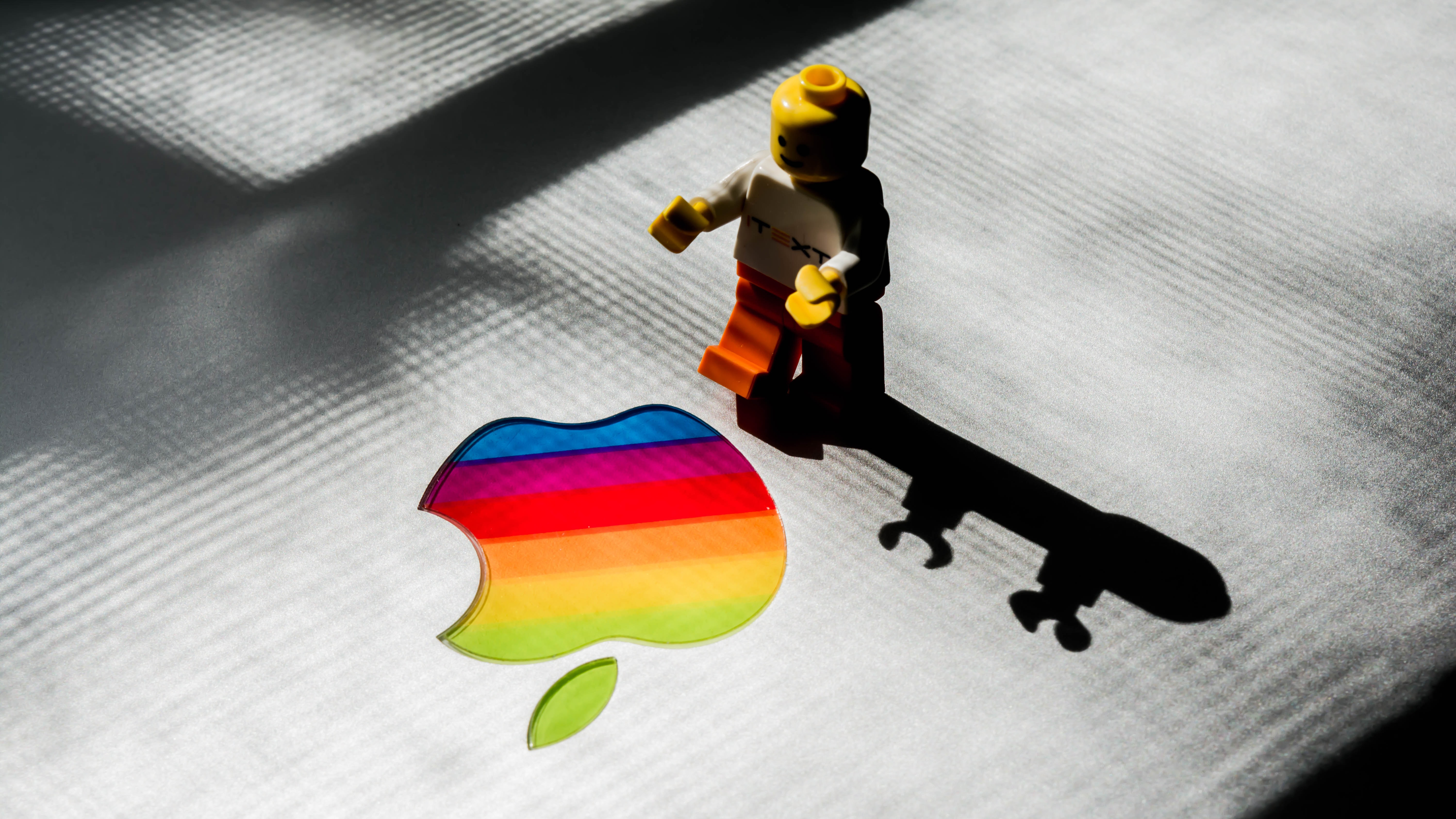 LEGO mini fig beside rainbow Apple logo