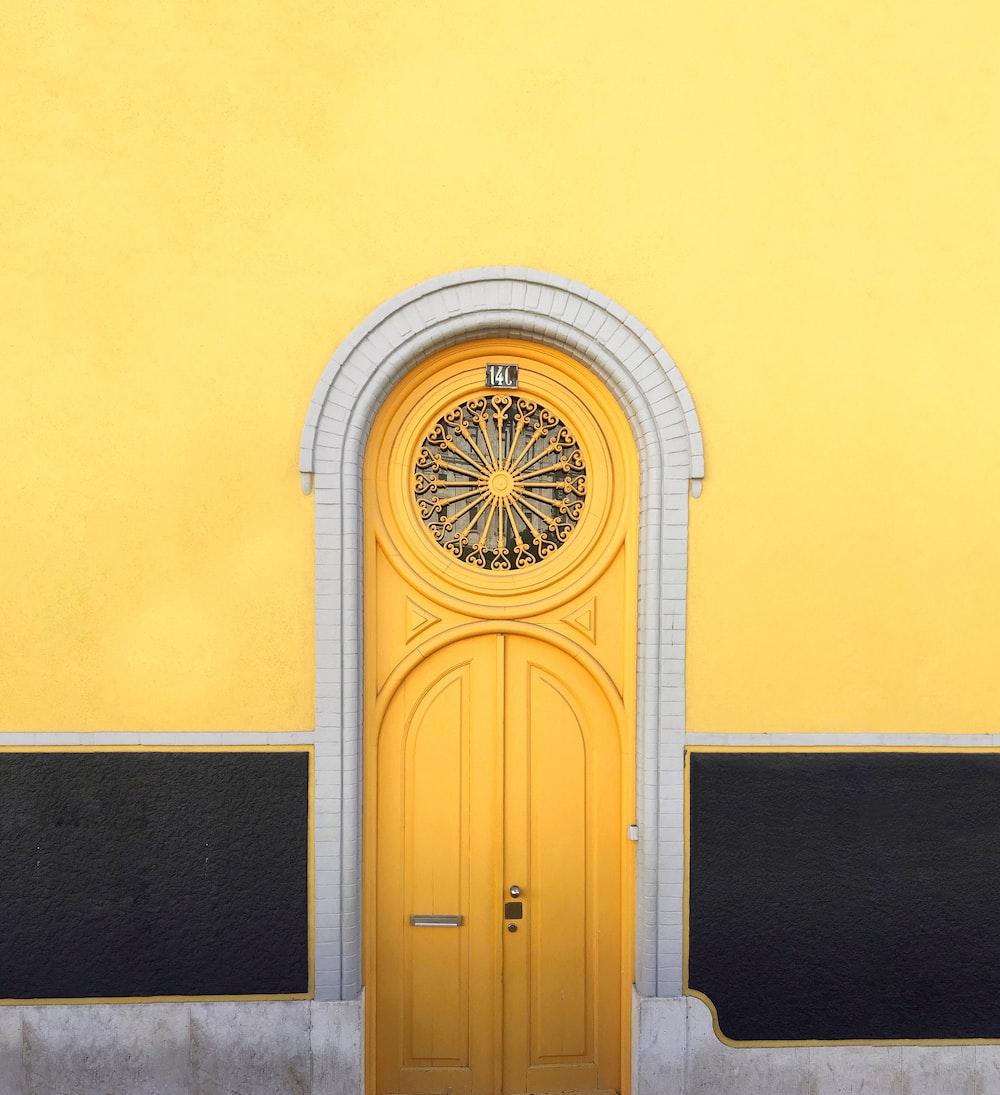 yellow wooden door between yellow wall