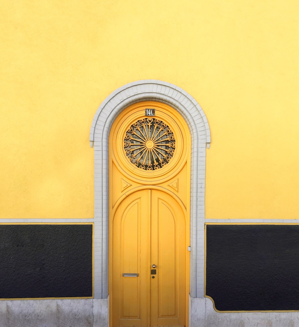 yellow wooden door between yellow wall