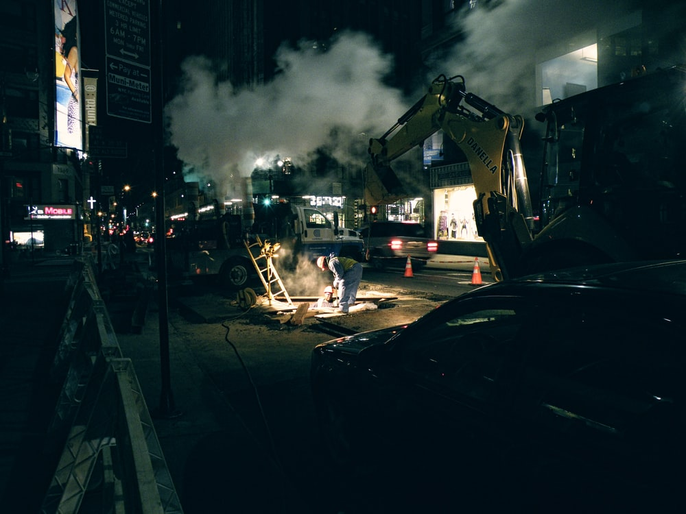 construction workers and vehicles on road during nighttime