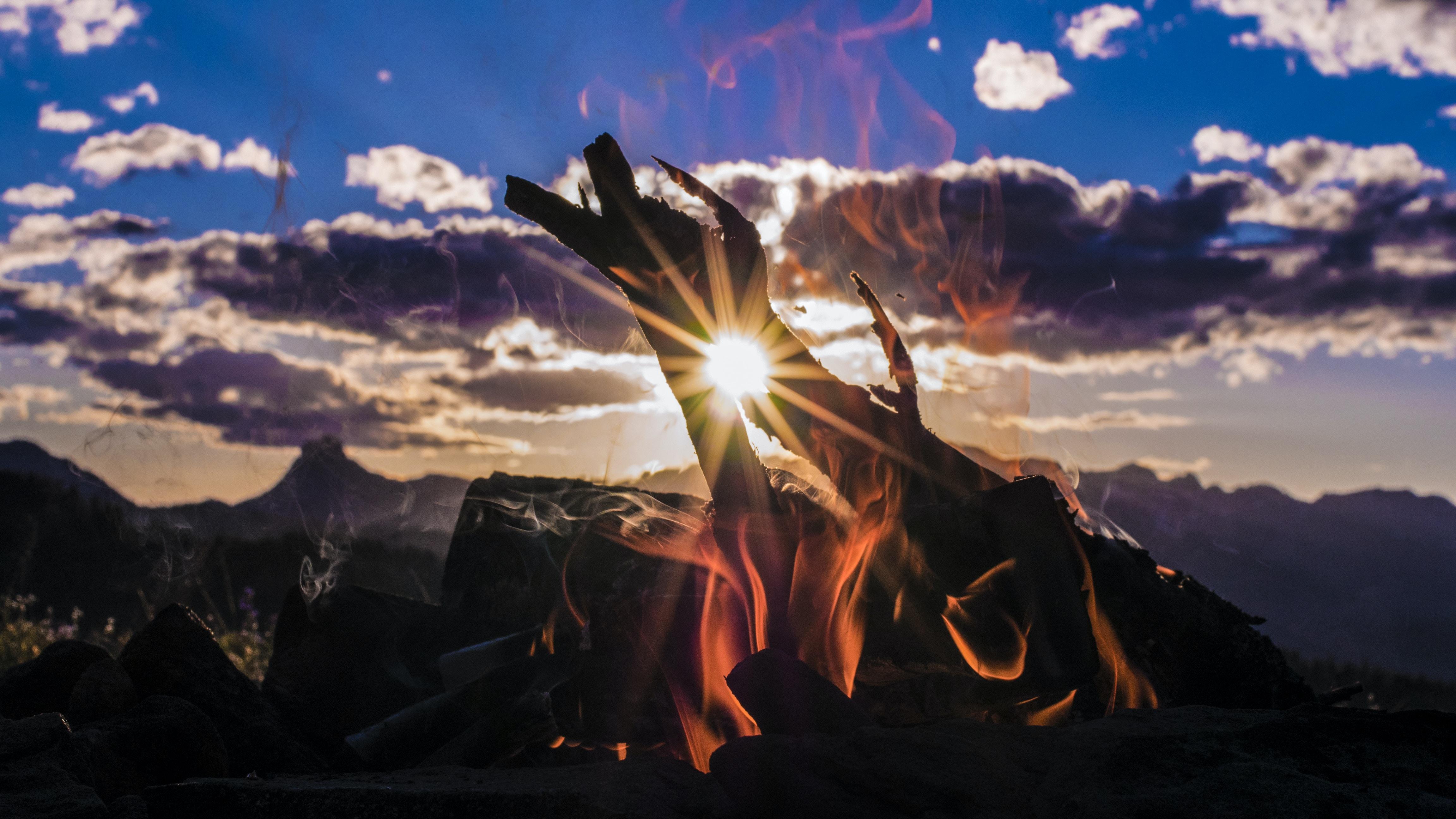 bone fire beside mountain with cloudy sky