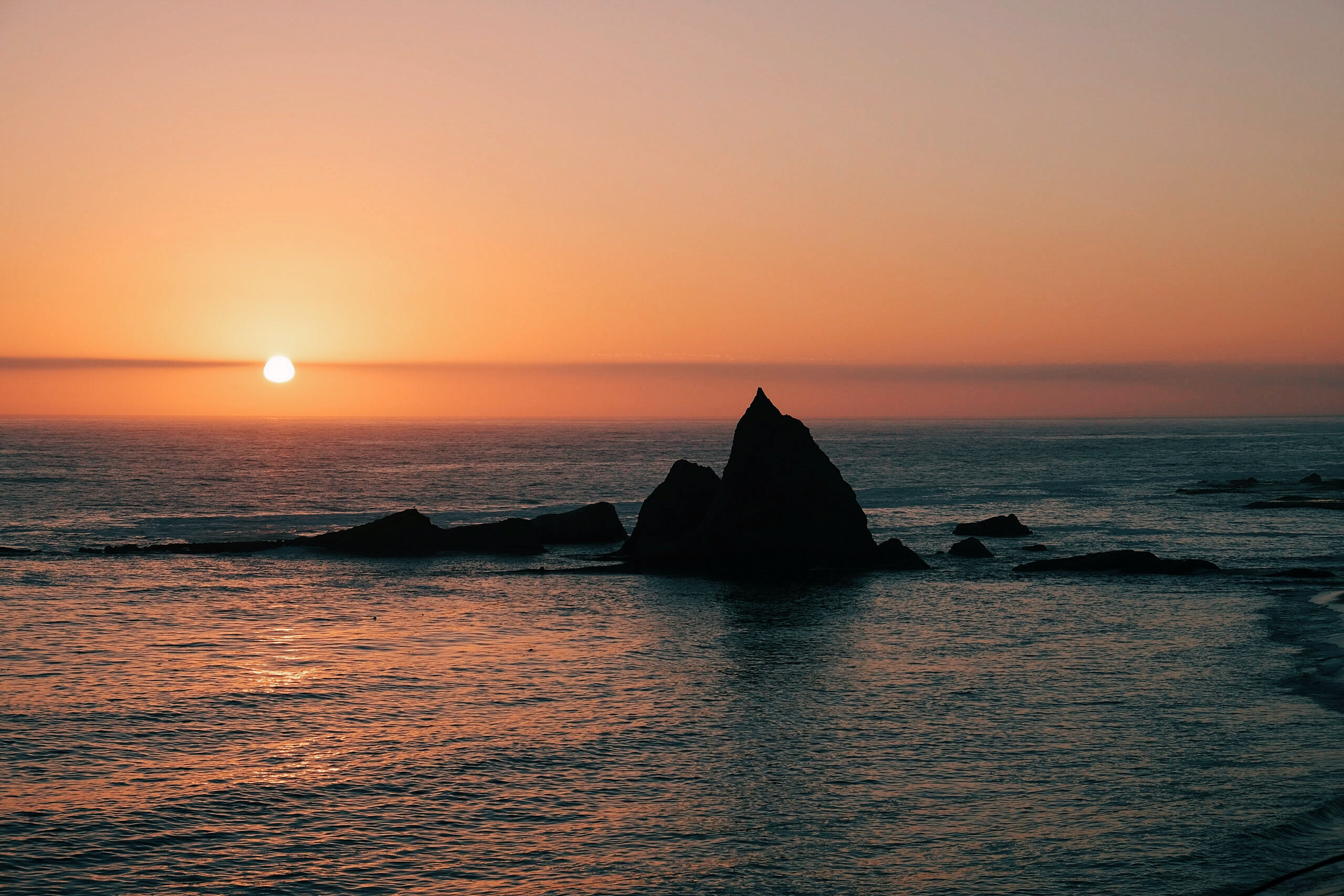 silhouette of rock formation surrounded by body of water at sunset