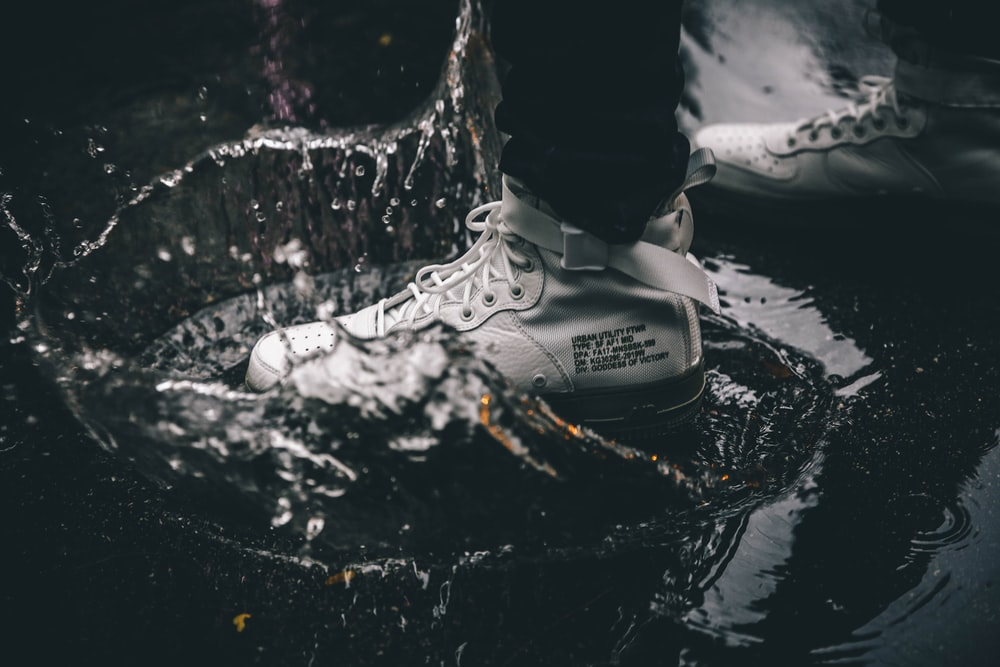 grayscale photography of person standing on water