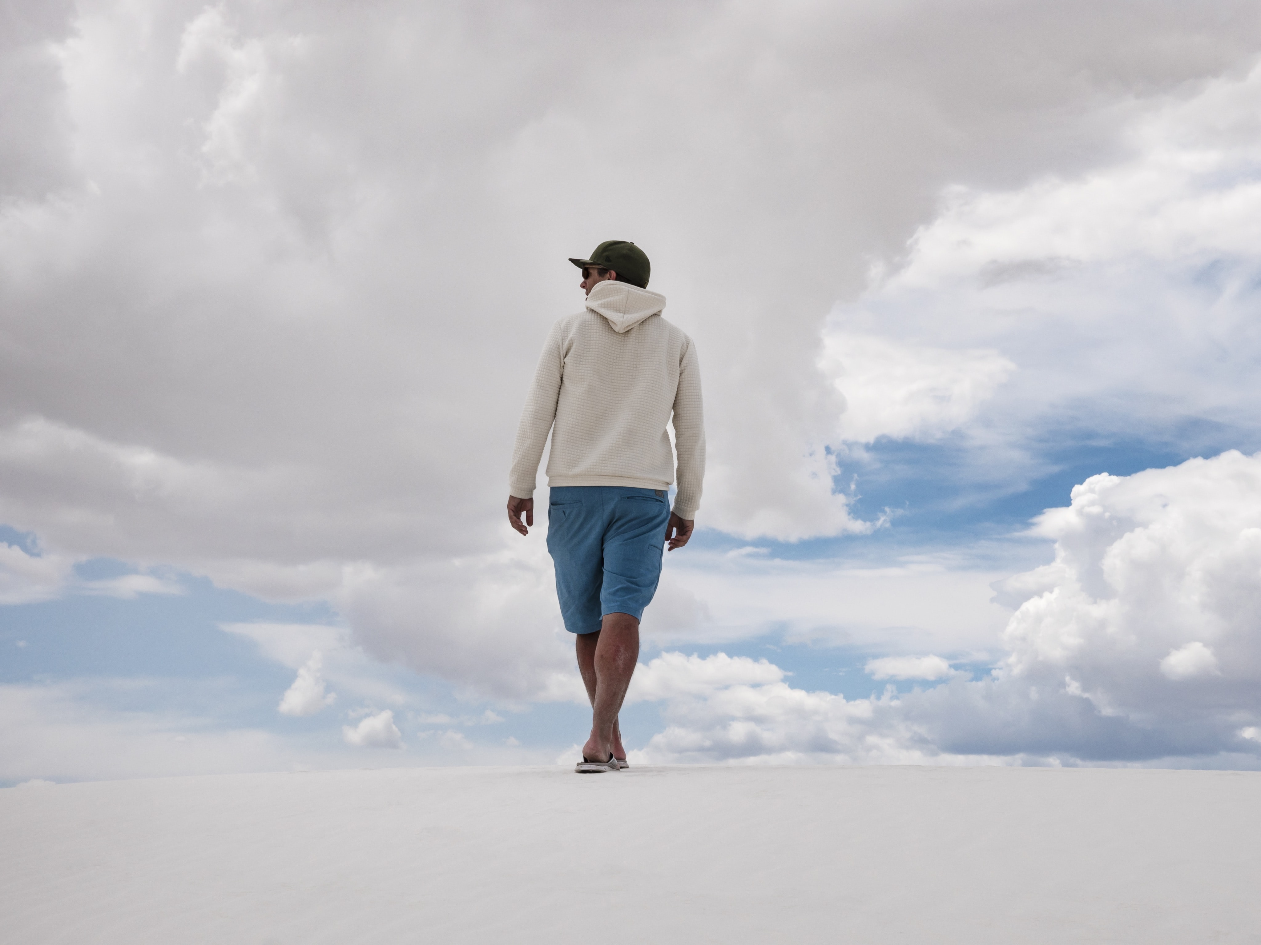 man walking on white surface under white clouds and blue sky during daytime