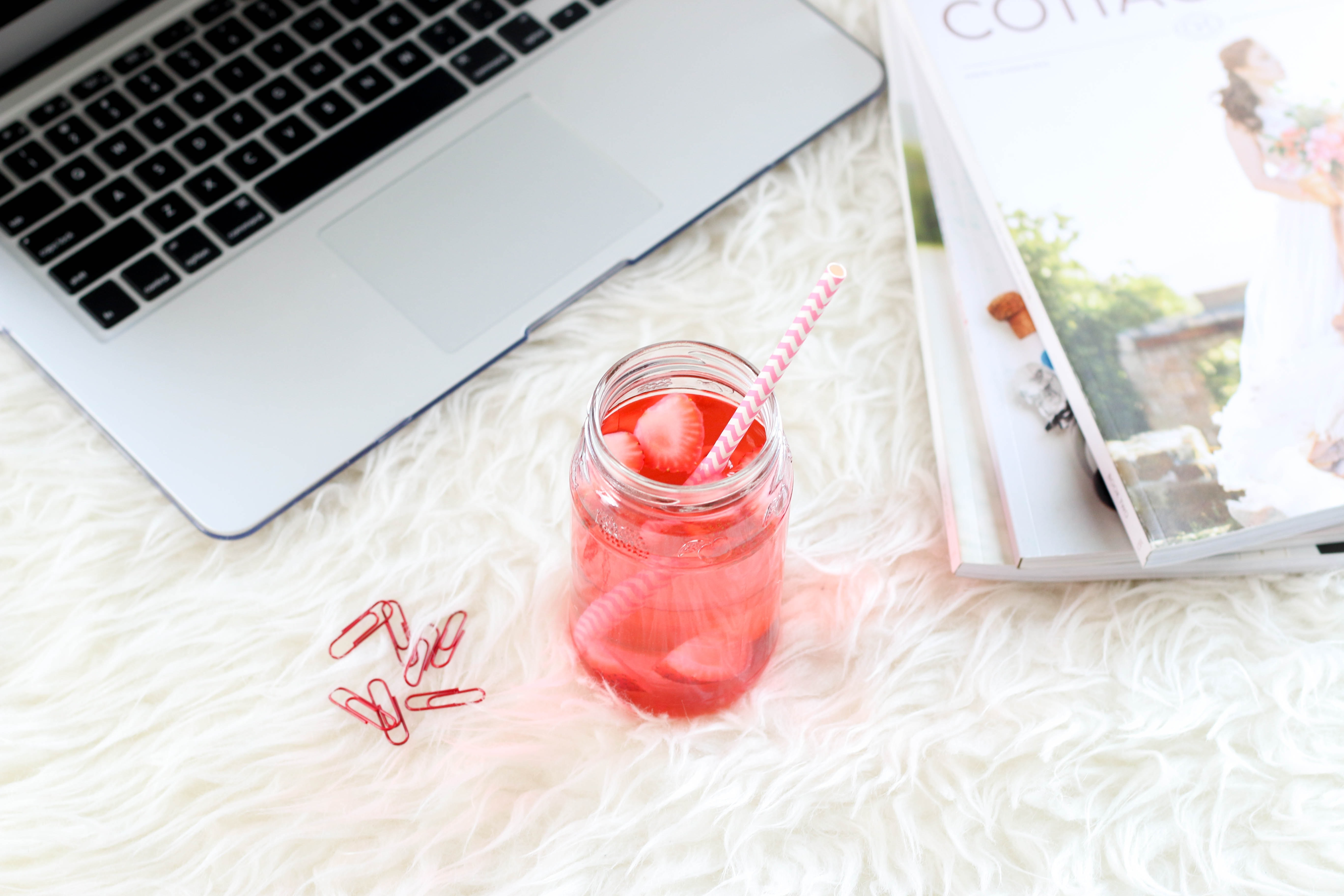 clear mason jar with red liquid and straw