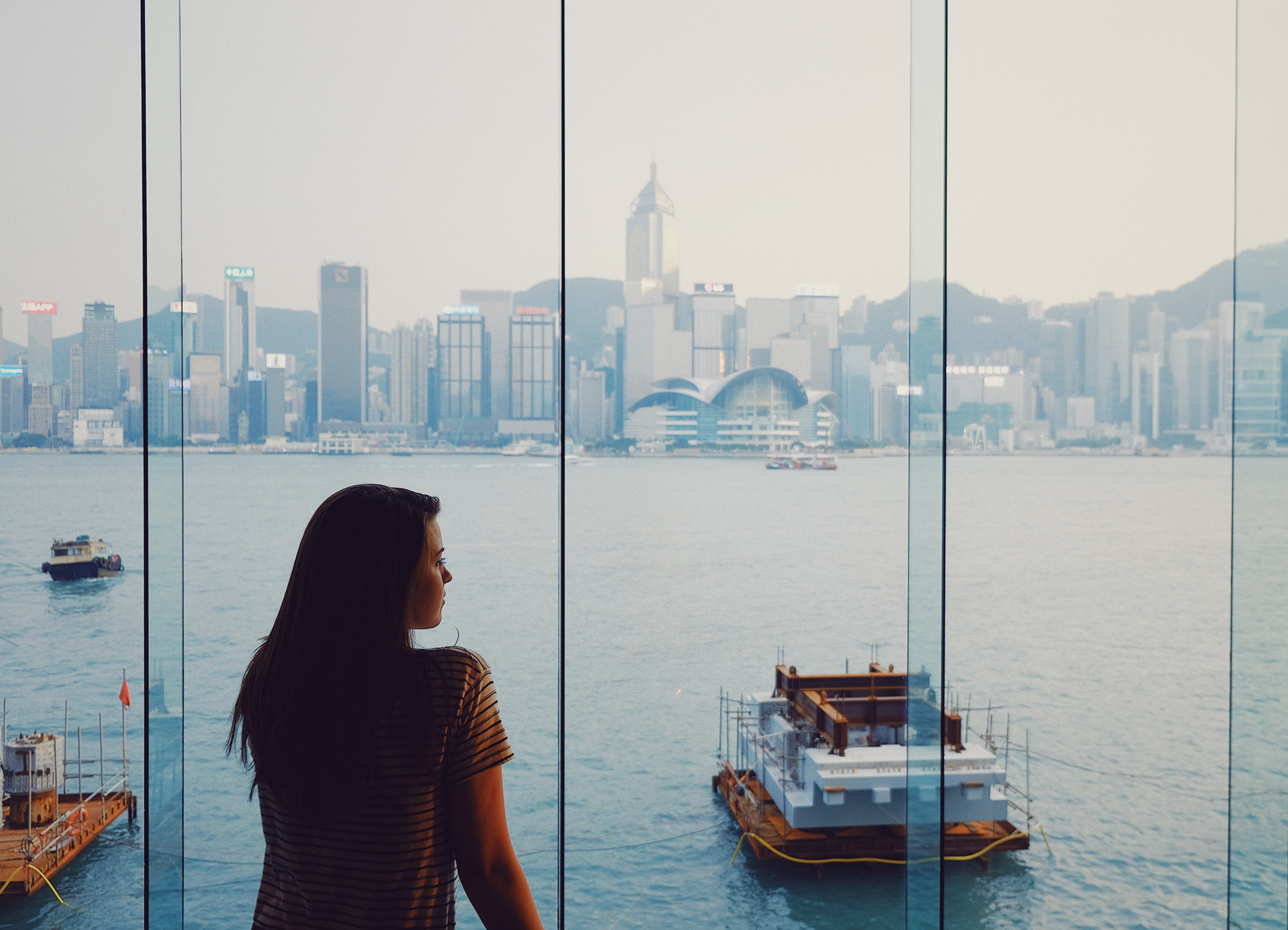 woman standing on glass window facing body of water