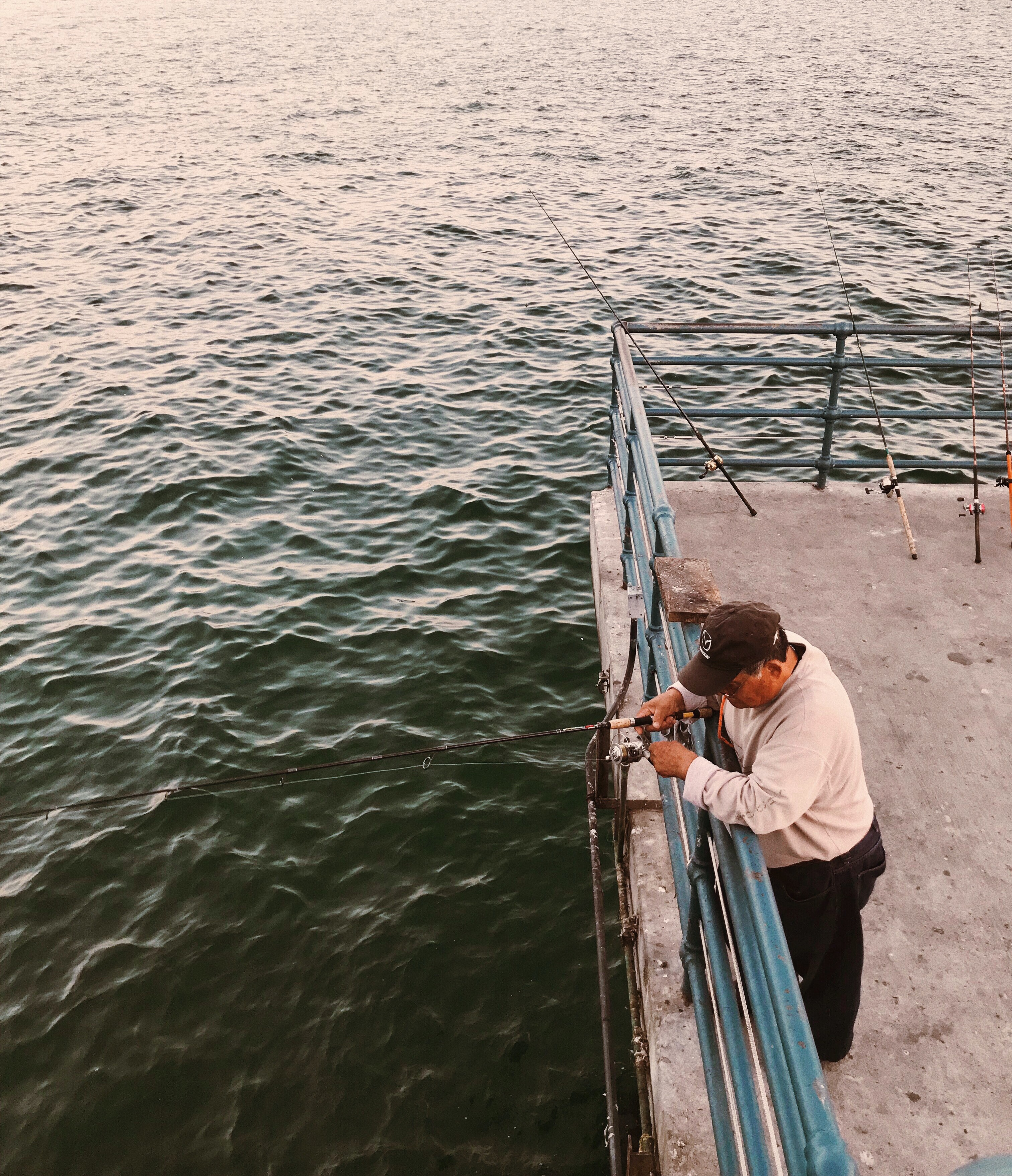 man holding black fishing rod standing on boat deck at daytime