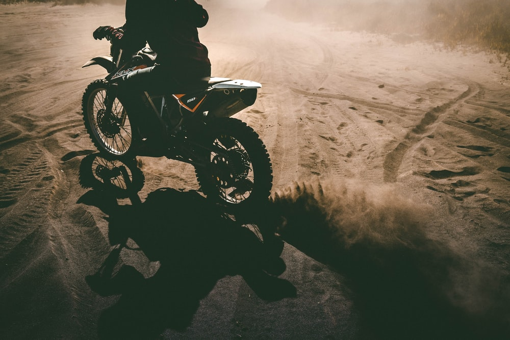 silhouette of man riding dirt bike