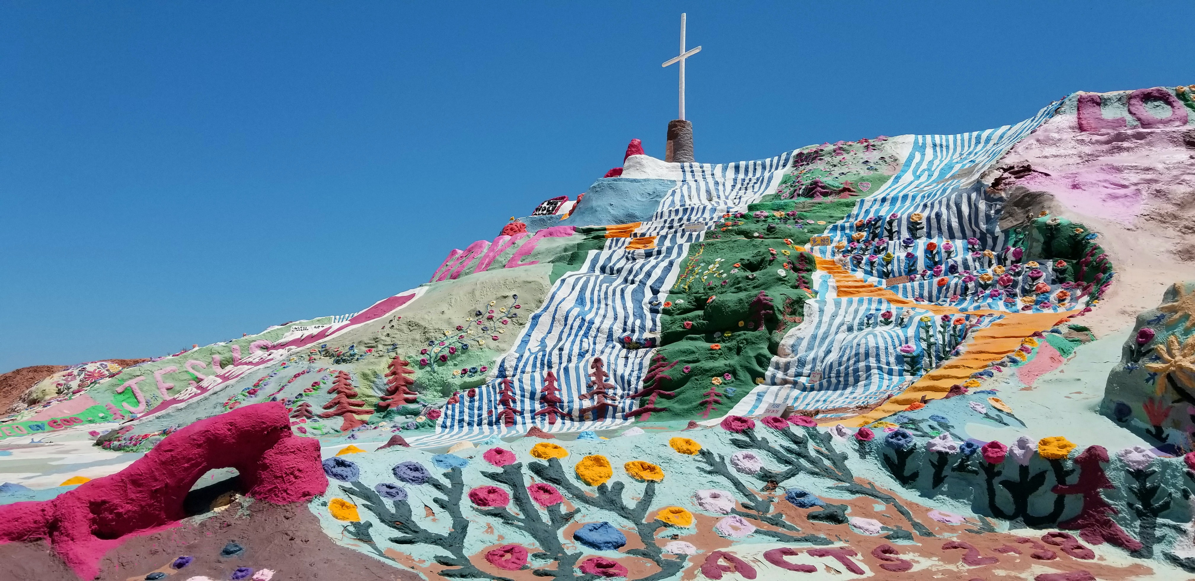 cross on top of multicolored hill